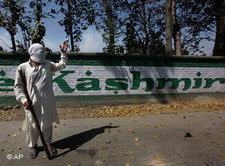 A masked Kashmiri protester signals to fellow protesters as they block the road during a protest against the arrest o