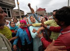 Kashmiri men try to stop women from joining the funeral procession of Fayaz Ahmed as they leave with the body from his house in Srinagar, India, Saturday, Sept. 18, 2010. Ahmed succumbed to injuries at a hospital after he was wounded in a protest last week (photo: AP)