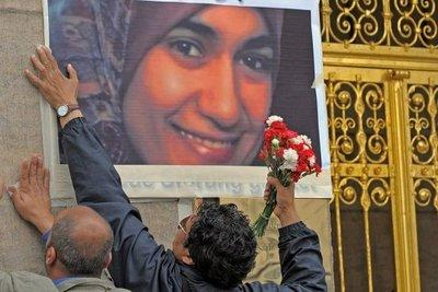 Two men affix a picture of Marwa El-Sherbiny on a wall (photo: dpa)