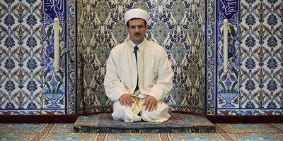 An imam kneeling in front of a prayer niche (photo: dpa)