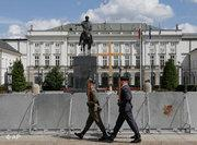 Soldiers march in front of the cross outside Poland's presidential palace (photo: AP)