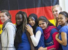 Young Germans in front of Germany's national flag (photo: picture-alliance/dpa)