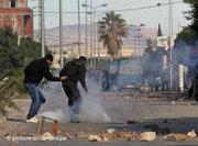 Young demonstrators throwing stones at security forces in Regueb (photo: AP)