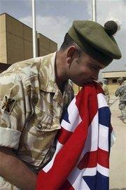 A British soldier kisses the UK flag during a hand-over ceremony to American forces in Basra (photo: AP)