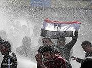 An Egyptian protester flashes Egypt's flag as anti-riot policemen use water cannons against protesters in Cairo (photo: dapd)