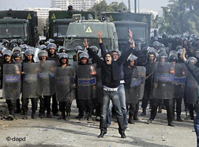 An Egyptian protester shouts in front of anti-riot policemen blocking a bridge in Cairo (photo: dapd)