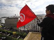 A protester waves the Tunisian flag as he watches a demonstration in Tunis (AP/dapd)
