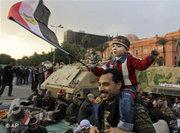 An Egyptian man carrying his son on his shoulders during a demonstration in Tahrir Square (photo: AP)