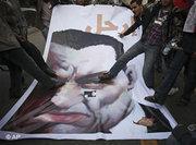 Jubilant demonstrators stamp on a poster depicting Mubarak in Cairo (photo: AP)