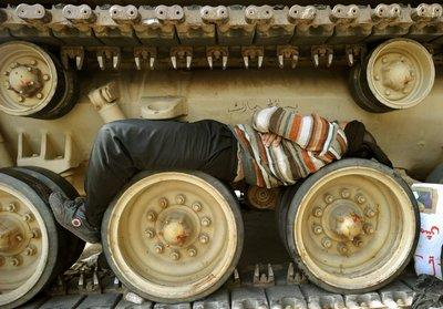 A demonstrator sleeping on a tank's wheels in Tahrir Square (photo: dpa)