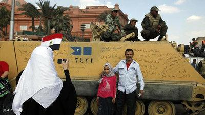 Demonstrators in Tahrir Square taking souvenir photos in front of tanks (photo: AP)