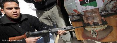 Libyan points a machine gun at a poster showing Gaddafi (photo: dpa)