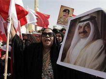 Portraits of Bahraini Prime Minister Khalifa bin Salman Al Khalifa and King Hamad bin Isa Al Khalifa are being held up during a pro-government demonstration (photo: Hassan Ammar/AP)