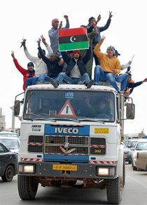 Insurgents are celebrating their victory in Benghazi by driving through town on the top of a truc