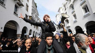 Young woman with a megaphone and protesters during an anti-regime demonstration in Rabat in February (photo: picture alliance/dpa)