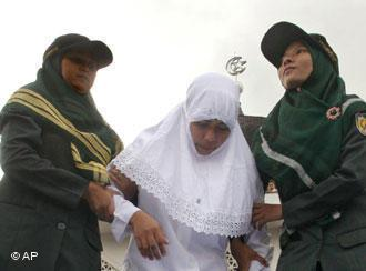 A woman receives physical punishment in  line with shariah law in Banda Aceh (photo: AP)