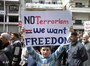 """Boy holding up a sign that reads """"No Terrorism. We want Freedom"""" (photo: AP)"""