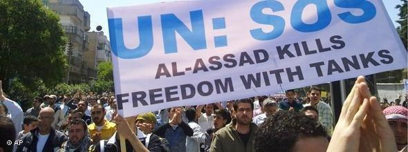 Syrian protesters hold a poster saying 'Assad kills freedom with tanks' (photo: AP)