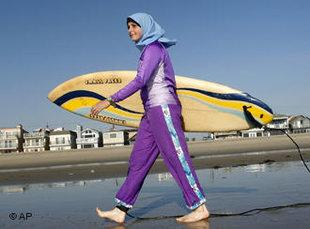 Girl wearing a headscarf, carrying a surfboard (photo AP)