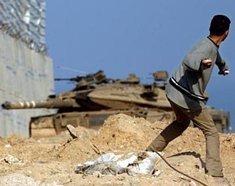 A Palestinian throwing rocks at an Israeli tank in West Bank (photo: AP)