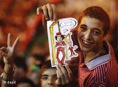 Teenage boy holds up a cartoon of Gaddafi at the gallows (photo: dapd)