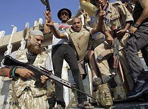 Rebel fighters gesture and shoot in the air as they celebrate overrunning Moammar Gadhafi's compound Bab al-Aziziya in Tripoli, Libya, early Wednesday, 24 August 2011 (photo: dapd)