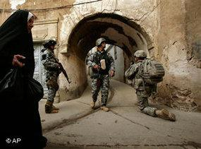 An Iraqi woman passes U.S. troops and Iraqi police officers as they stand guard in the Bab al-Jadeed area of Mosul, 360 kilometers (225 miles) northwest of Baghdad, Iraq, Thursday, 23 April 2009 (photo: AP)