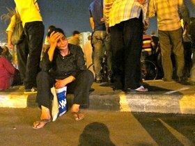 A woman sitting on the sidewalk after the violence on Sunday (photo: Joseph Mayton)