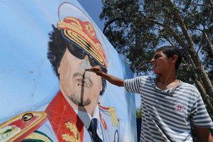 Junger Mann karikiert Bildnis Gaddafis; Foto: dpa