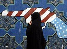 A woman walking past a mural of a pistol in the colours of the American flag (photo: dpa)