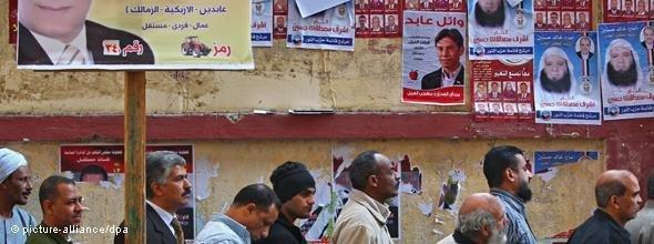 Men standing in line beside a wall plastered with Egyptian election posters (photo: picture alliance/dpa)