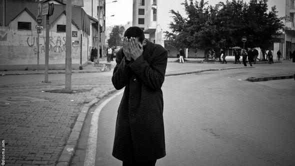 Man holding his head in his hands on a a Tunis street (photo: Selim Harbi)