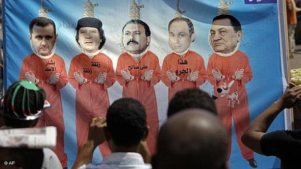 Egyptian protesters photograph a banner showing, right to left, ousted Egyptian President Hosni Mubarak, his son Gamal, Yemeni President Ali Abdullah Saleh, Libyan leader Moammar Gadhafi and Syrian President Bashar Assad, at Tahrir Square in Cairo, 15 July 2011 (photo: AP)