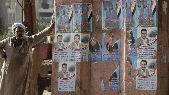 Man standing next to a wall with candidate posters of the Nour Party (photo: AP)