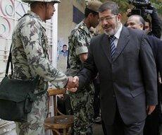 Muslim Brotherhood spokesman Mohammed Morsi shakes hands with a solider (photo: AP)