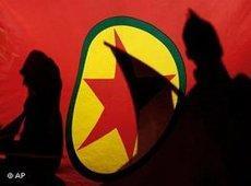 Shadows seen against the flag of the PKK (photo: AP)