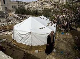 A Palestinian woman stands next to a tent set up in the spot where Israeli authorities demolished a house in the east Jerusalem neighborhood of Silwan (photo: AP)