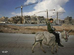 A Palestinian child rides a donkey past construction of new housing units in the Israeli neighborhood of Har Homa in the eastern part of Jerusalem, Sunday, 9 December 2007 (photo: AP)