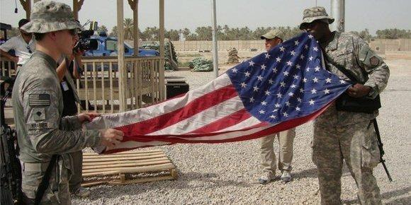 American soldiers fold the US flag on their military base in Iraq (photo: dpa)