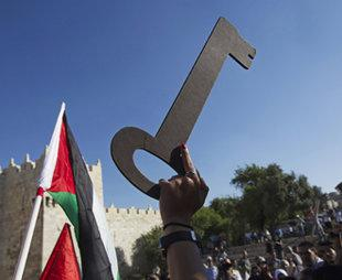 A woman holds up a large cardboard key on May 15, the