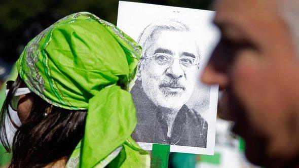 Green Revolution activists hold up a poster of Mir-Hossein Moussavi, leader of the movement (photo: AP)