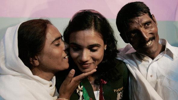 Nasreen (left) and Abdul Hameed flank their daughter Naseem, who won the gold medal in the women's 100-metre race at the 11th South Asian games in 2010 (photo: ddp images/AP Photo/Shakil Adil)