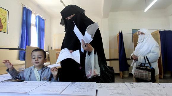 Woman in a Niqab and a boy at the election box (photo: dpa/picture-alliance)