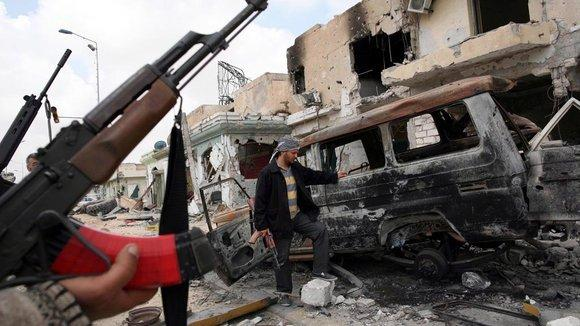 Lybian rebels in Misrata standing in front of a damaged car (photo: picture alliance/dpa)