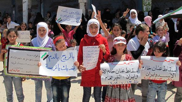 Girls hold signs and shout slogans against Syria's President Assad in Bennish, near Idlib (photo: REUTERS/Abdo)