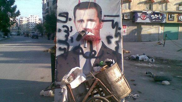 A poster of Bashar al-Assad covered in graffiti in the city of Aleppo (photo: Reuters)