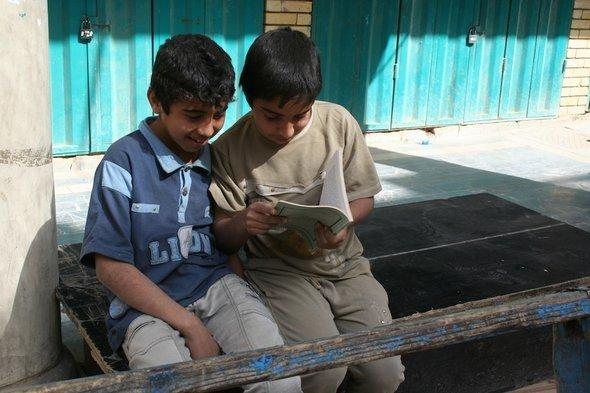 Two young boys reading a book on Mutanabbi Street in Baghdad (photo: Munaf al-Saidy)