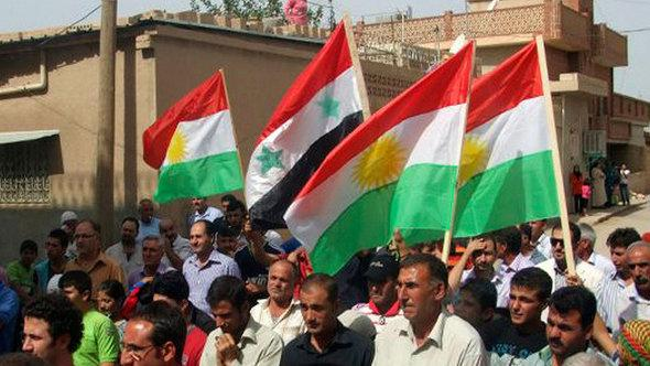 Syrian Kurds wave Kurdish and Syrian flags as they demonstrate against the Assad regime in Syria in September 2011 (photo: AP)