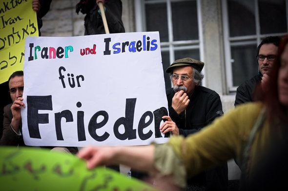 Demonstrators hold up a placard calling for peace (photo: Jakob Huber)