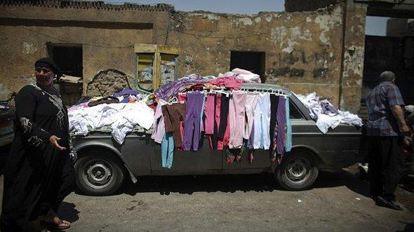 Clothes for sale on display on an old car in Ramlet Bulak (photo: AP)